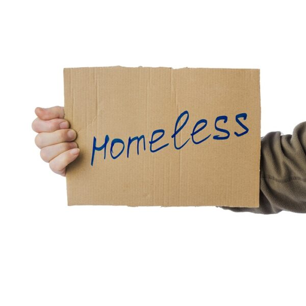 Homeless person holding cardboard sign