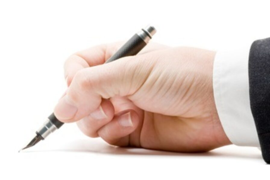 Photograph of person signing standard letter